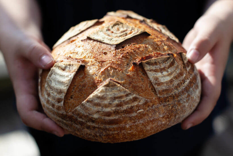 Tom holds freshly baked sourdough bread