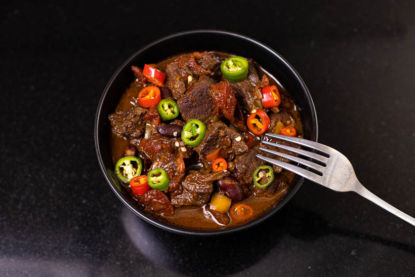 chili con carne on a black stone table