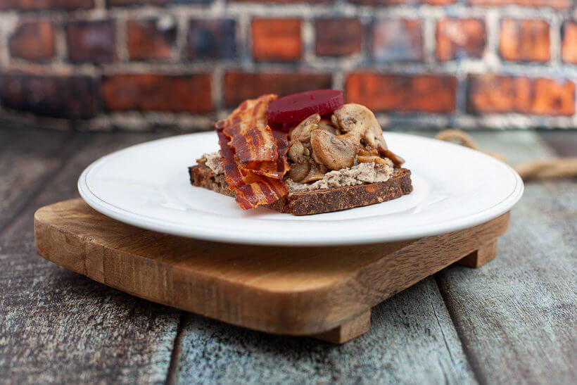Liver pâté on rye bread with mushrooms, crispy bacon and pickled beet root