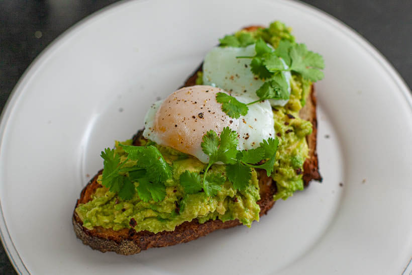 smashed avocado with poached egg sourdough sandwich