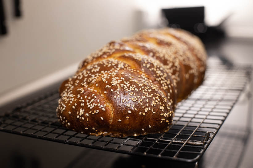 sourdough challah with sesame seeds cooling on a wire rack