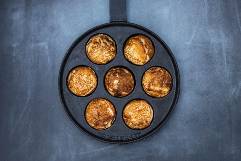 Pan of sourdough æbleskiver on a concrete flour seen from the top