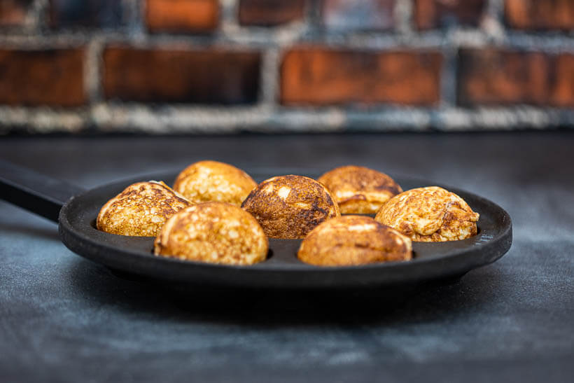 Pan full of sourdough æbleskiver in front of a brick wall