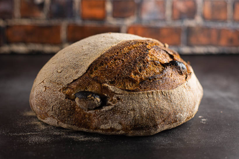 Sourdough olive bread on a concrete floor in front of a brick wall