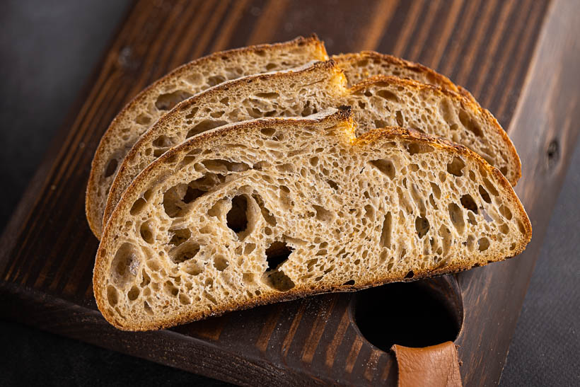 high hydration sourdough bread recipe with tangzhong - gorgeous crumb on a cutting board