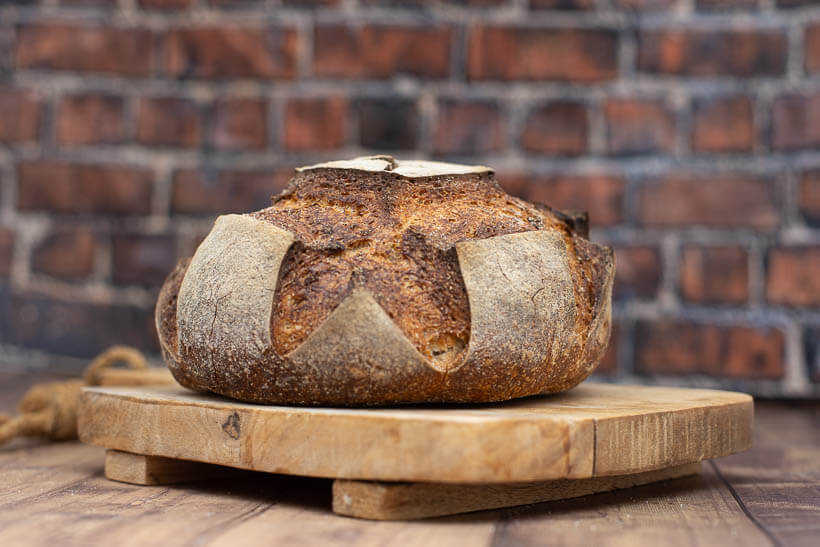 An artisan sourdough boule on a wooden board in front of a brick wall