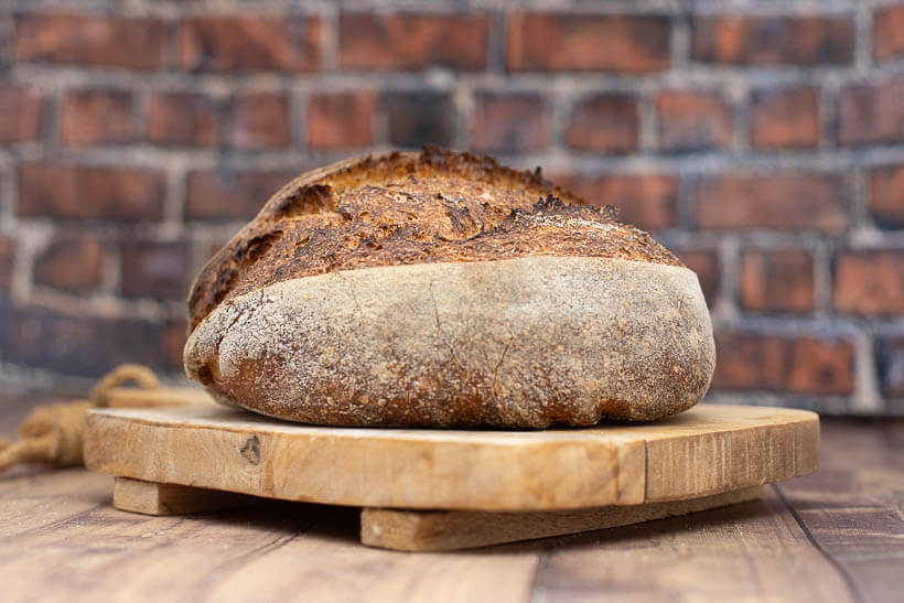 An artisan sourdough bâtard on a wooden board in front of a brick wall