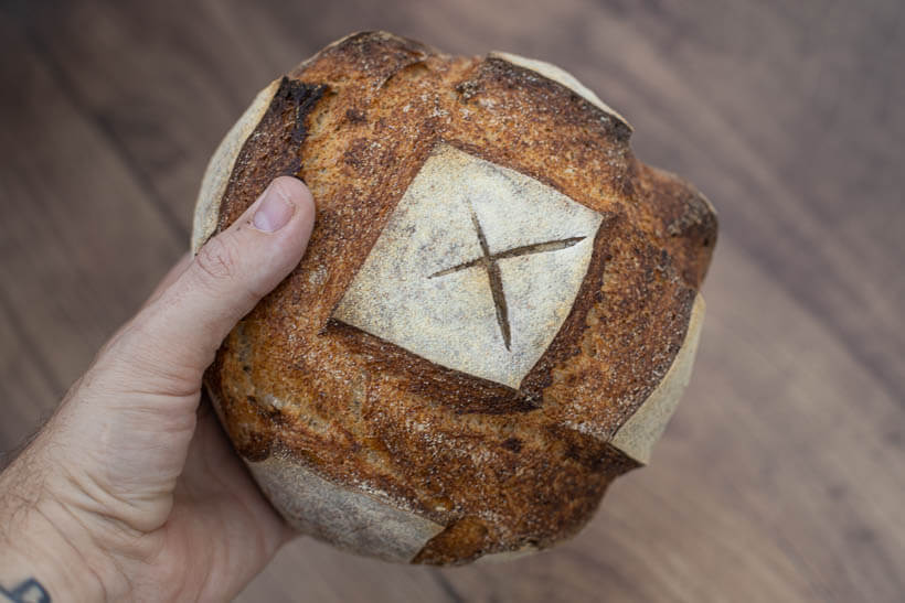 I hold an artisan sourdough bread made using my own hands