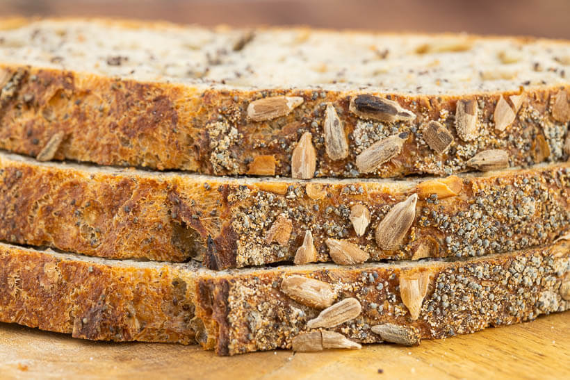 Three slices of sourdough bread with poppy seeds and sunflower seeds on the crust and in the crumb