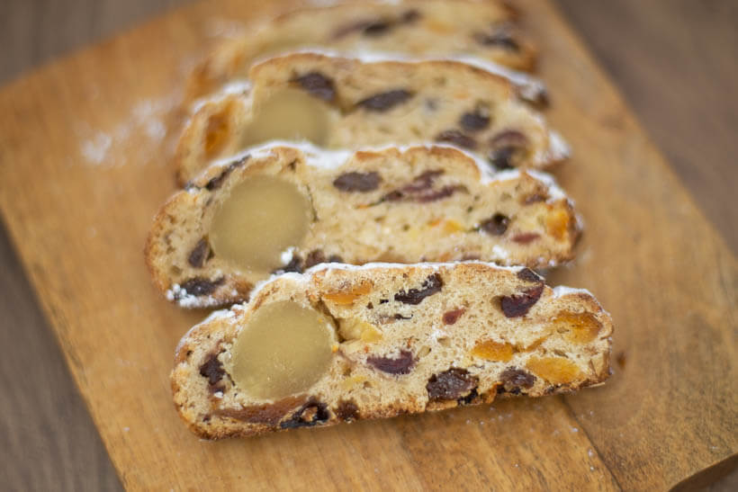 Slices of sourdough stollen with rum-soaked dried fruit and a roll of marzipan on a wooden board