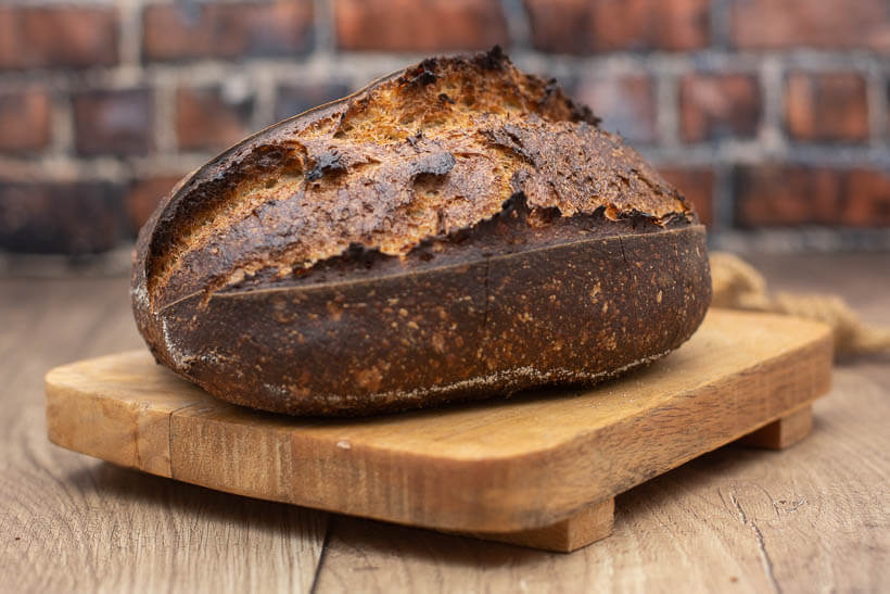 A sourdough bread on a wooden board in front of a brick wall