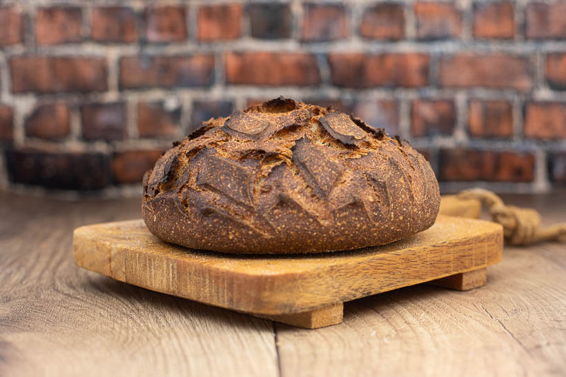 Sourdough Boule on a wooden board in front of a brick wall