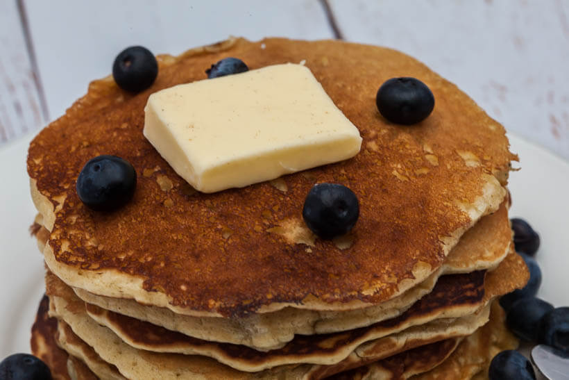 Closeup of a stack of pancakes with blueberries and butter on top