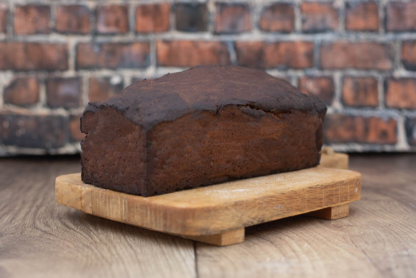 Limpa Bread on a wooden board in front of a brick wall