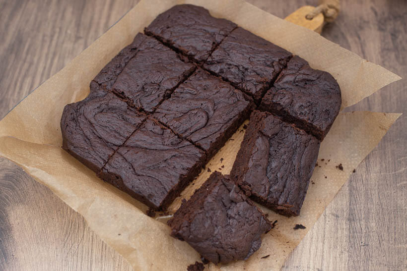 fudgy brownies on a piece of parchement paper