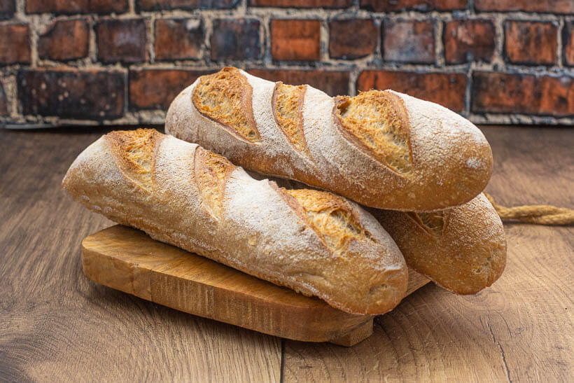 Sourdough baguettes on a wooden board in front of a brick wall