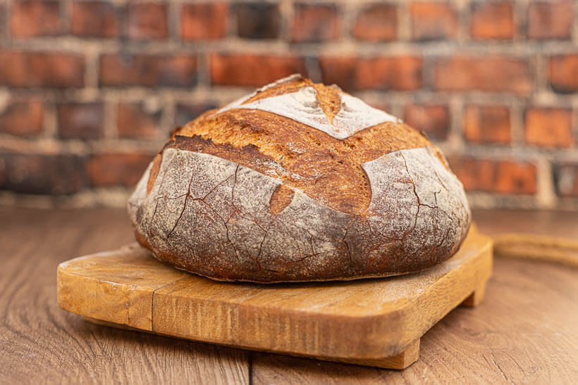 Crusty, yeasted artisan bread on a board in front of a brick wall